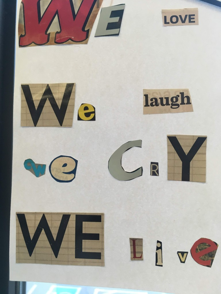 Cut out letters on a sign: We love, We Laugh, We Cry, We Live.