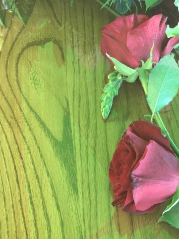 Heart-shaped grain in the wood of a casket with two red roses.