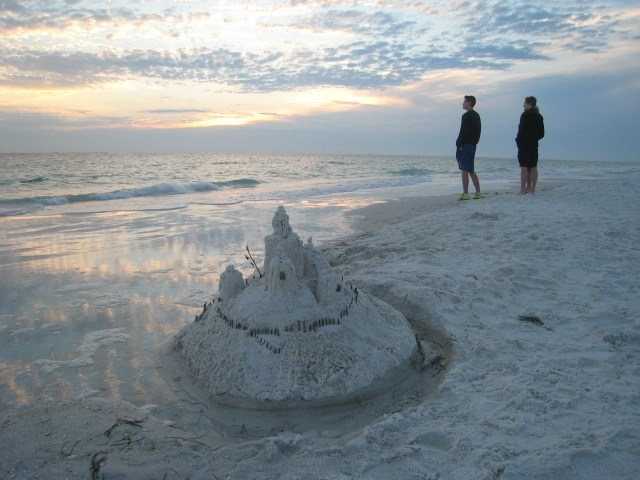 Sandcastle in foreground with the silhouettes of two teenaged boys in the distance