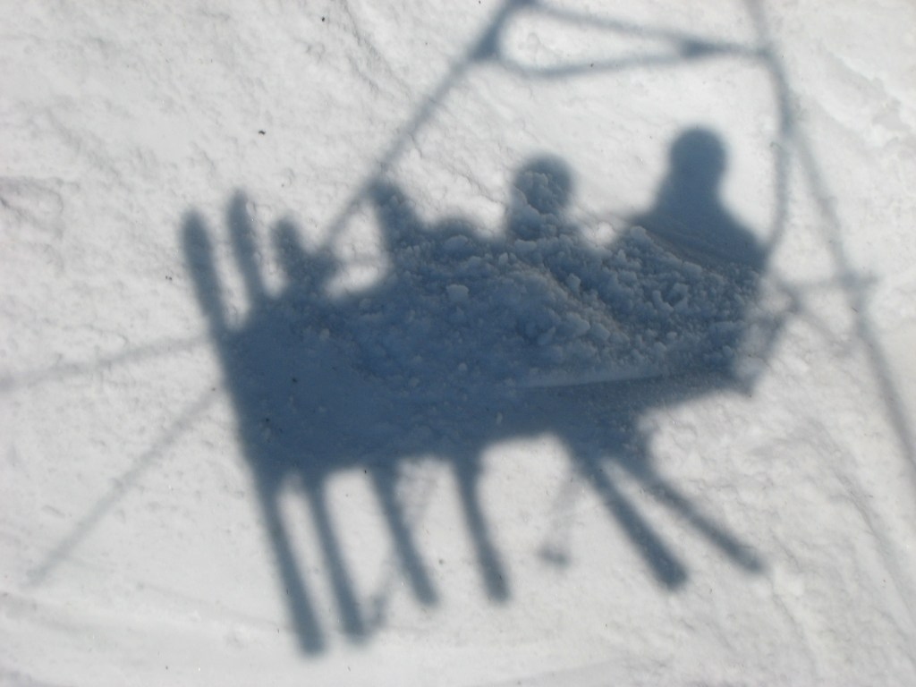 Shadow of skiers on a ski lift