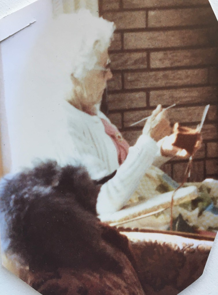 Woman knitting by the fire. Dog on the chair beside her.