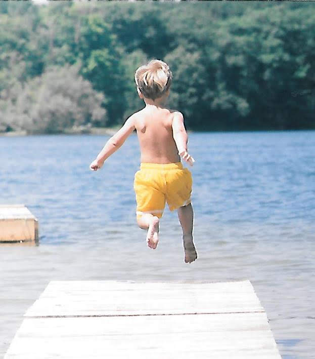 Boy jumping off dock into a lake.