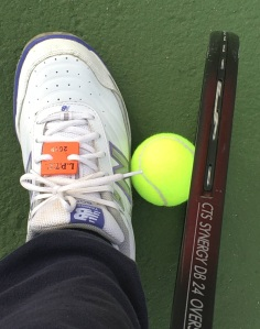Woman picking up tennis ball using a shoe and the racquet