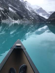 Tip of a canoe on the glacial green waters of Lake Louise, Alberta, Canada